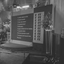 Fotografia in bianco e nero del tabellone segnapunti nel 1958;  i numeri dell'ordine di partenza e i titoli dei brani delle voci in competizione sono stampati sul lato sinistro del tabellone, mentre i numeri rotanti sul lato destro mostrano l'assegnazione dei punti a ciascuna canzone quando viene chiamata la giuria di ogni paese e un totale di tutti i punti ricevuti;  i titoli dei brani sono ordinati in base all'ordine di apparizione, con il primo brano da eseguire che appare nella parte superiore del tabellone.