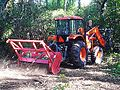 Fecon PTO-driven mulching attachment on tractor.jpg