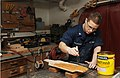 Flickr - Official U.S. Navy Imagery - A Sailor adds wood stain to a plaque. in the wood shop..jpg