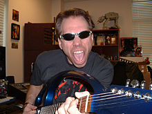Musician Frank Klepacki holding the neck of his guitar to the camera wearing sunglasses, collectibles on shelves in the background