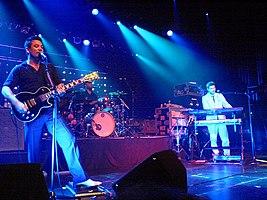 Una guitarra de tres piezas tocando en vivo.  Morgan se para al frente del escenario, tocando la guitarra y con la boca hacia un micrófono en un soporte.