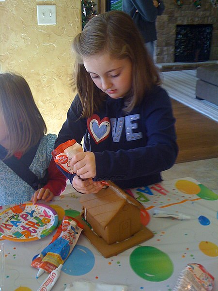 File:Girl decorates gingerbread house.jpg