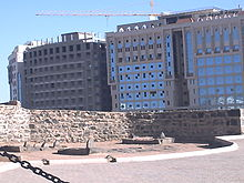 Low stone wall with remains of sarcophagi next to modern buildings