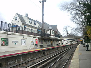 Great Neck (LIRR station) - The Great Neck station as seen from the Port Washington-bound platform. The depot is visible above the canopy for the Penn Station-bound platform.