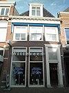 foto van Huis met eenvoudige gevel; omlijste deurpartij met bovenlicht; bescheiden versierde kroonlijst