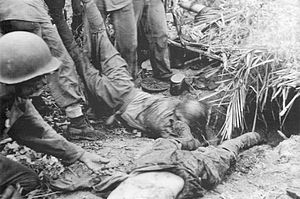 Matanikau Offensive - U.S. Marines drag the bodies of dead Japanese soldiers from their bunker in the Point Cruz area after the battle in early November.