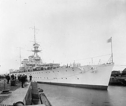 HMS Hawkins, lead ship for her class of heavy cruisers alongside a quay, probably during the interwar period HMS Hawkins quayside.jpg