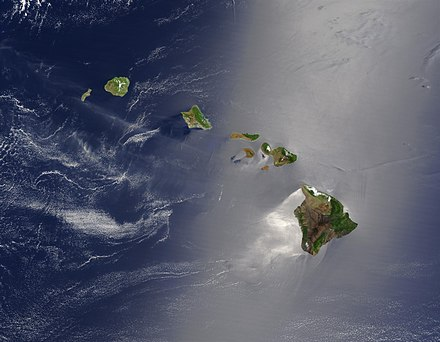 A true-color satellite view of Hawaii shows that most of the vegetation on the islands grows on their northeast sides, which face the wind. The silver glow around the southwest of the islands is the result of calmer waters. Hawaje-NoRedLine.jpg