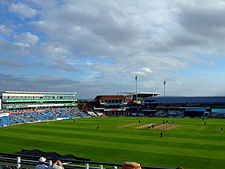 A panoramic view of a cricket ground with players occupying the field