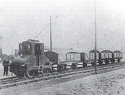 The driver stands beside a small electric locomotive towing four coal wagons