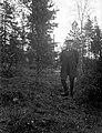 Helporträtt av en pojke i överrock, knäbyxor, långstrumpor och skärmmössa i en skogsglänta - Nordiska Museet - NMA.0057478.jpg