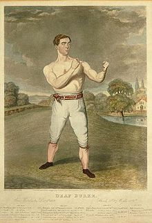 A newspaper clipping featuring James Burke, with white trousers and a black belt, in fighting stance. He has short brown hair and fair complexion.