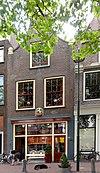 foto van Pand met klokgevel met zijvoluten. Top verdwenen. Metselwerk vernieuwd XIX a. Gevelsteen: leeuw in de tuin van Holland, gepolychromeerd.