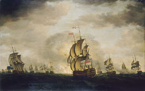 An oil painting depicting a sea battle. The sky has dark clouds with patches of blue, and the sea is grey. Warships are visible in the distance, some of which are exchanging cannon fire. A British warship occupies the center foreground, obscuring an explosion behind it.