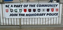 A recruiting banner for the Honorary Police showing the arms of each parish: (from left to right) Grouville, St Brelade, St John, Trinity, St Saviour, St Ouen, St Helier, St Mary, St Lawrence, St Clement, St Peter, St Martin Honorary Police banner Jersey.jpg