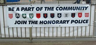 Parishes of Jersey - A recruiting banner for the Honorary Police showing the arms of each parish: (from left to right) Grouville, St Brelade, St John, Trinity, St Saviour, St Ouen, St Helier, St Mary, St Lawrence, St Clement, St Peter, St Martin