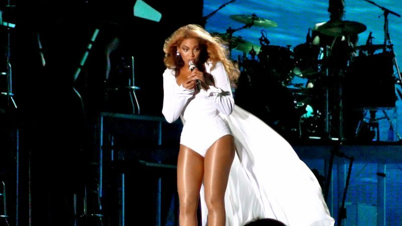A brunette woman is singing while she holds a microphone with both hands. She wears a white short dress that has a long cape and sheer stockings. The background is blue and a drum kit and a drummer are visible.