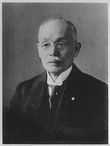 A black-and-white photograph of a Japanese man looking left