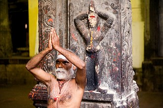 Añjali Mudrā - A sadhu performing Anjali Mudra at his crown chakra in front of a sculptured figure in the same posture