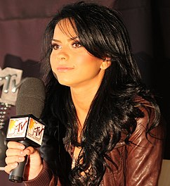 A photograph of Inna wearing a brown jacket and holding a microphone in her hand.