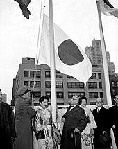 Un grupo de hombres y mujeres que miran una bandera que se plantea.