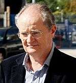 A portrait of a bespectacled, balding male in his late fifites. He is wearing a black coat over an unbuttoned light blue collared shirt.