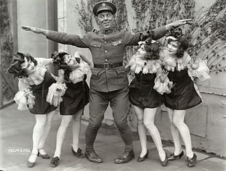 Karl Dane - Karl Dane, wearing the U.S. Army sergeant's costume for the 1927 film Rookies, demonstrates how he towers over four chorus girls in an MGM publicity still.