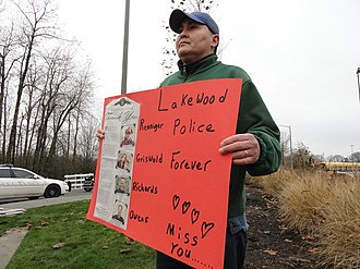 2009 Lakewood shooting - Above, Lakewood police Chief Bret Farrar commemorates the Lakewood Police Department Fallen Officer Memorial in 2010. Below, a man holds up a sign in honor of the victims at that commemoration ceremony.