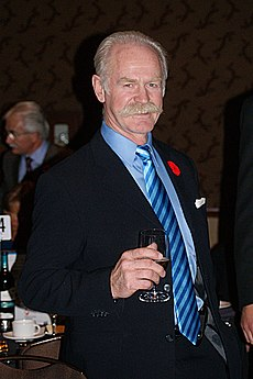 A grey-haired, grey-moustached man holds a wine glass.  He is wearing a blue suit with a striped blue tie