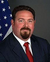 A photograph of a man with a goatee looking at the viewer while wearing a navy suit jacket, a white dress shirt, and a red necktie