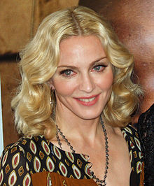 A closeup photo of Madonna with shoulder-length wavy blonde hair, heavy makeup and a colorful, low-cut blouse.