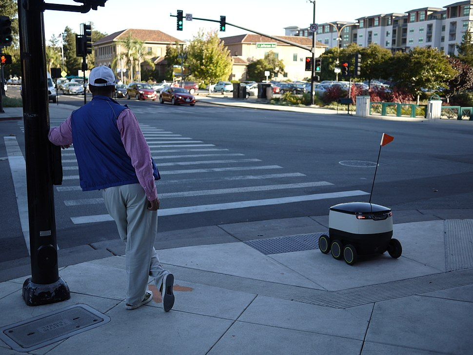 Man and delivery robot waiting at pedestrian crosing in Redwood City, California