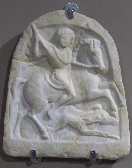 """Thracian horseman"" votive tablet with the standard iconographic elements: the rider is holding a lance in his right hand aiming at a boar attacked by a hunting dog. Marble votive tablet of a Thracian horseman.jpg"