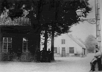 Zicht op de Markt te gemeente Deurne vanuit de Kerkstraat (toen nog Haageind), 1890. De man rechts zit op de schamppaal van het oude raadhuis.