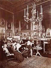 Photographie en noir et blanc d'une Victoria âgée assise à côté d'une jeune femme (Beatrice) lisant un journal. La pièce est richement décorée avec de nombreuses photographies et peintures et un large chandelier est suspendu au plafond.