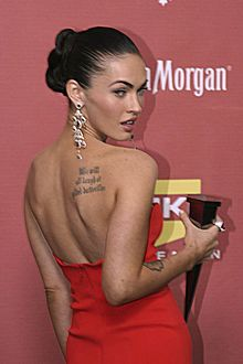 An image of a young woman with her back toward the camera. She is turning her head toward the camera, and is holding an award. She is wearing a low-cut red dress, which exposes a back tattoo.