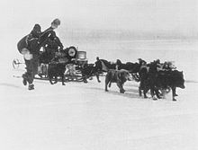 Two men in polar gear drive a sledge dog team pulling a heavily laden sledge
