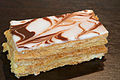 A French pastry called Mille-feuille that has layers of pastry topped with chocolate and vanilla swirled icing.
