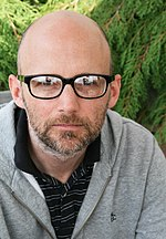 A bald man with glasses is looking intently at a camera.