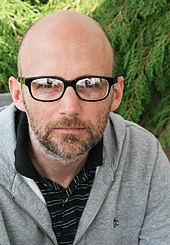 A bald man in glasses, looking directly to the camera