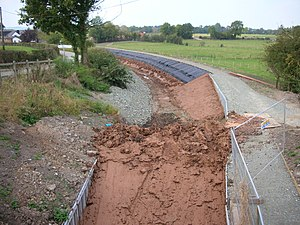 Puddling (civil engineering) - New puddle lining to the sides of a restored section of the Montgomery Canal at Redwith Bridge. A huge plug of puddle clay temporarily blocks the end of the canal