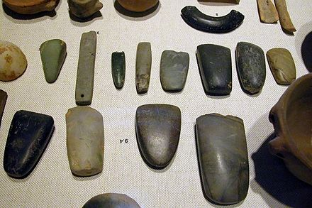 An array of Neolithic artifacts, including bracelets, axe heads, chisels, and polishing tools