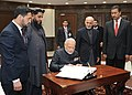 Narendra Modi writing on the visitors' book at newly inaugurated Parliament Building of Afghanistan, in Kabul on December 25, 2015. The President of Afghanistan, Dr. Mohammad Ashraf Ghani is also seen.jpg