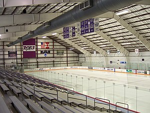 The inside of an ice hockey arena. An empty ice hockey surface is at the base of rows of spectator benches.