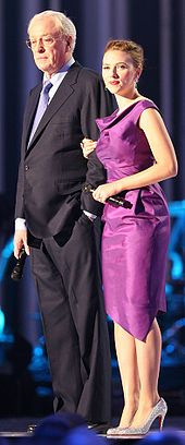 A older man with gray hair, wearing glasses and dressed in a black suit and matching lavender shirt and tie stands on a stage in front of a dark curtain. A young woman with blonde hair pulled away from her face, wearing a sleeveless purple dress and high heels stands next to him, her right hand holding his left arm. Both are holding cordless microphones. There is blue backlighting that reflects off of the floor.