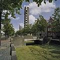 Overzicht kerk met slanke opengewerkte toren, op de voorgrond een gedeelte van de gracht - Almere-Haven - 20410307 - RCE.jpg