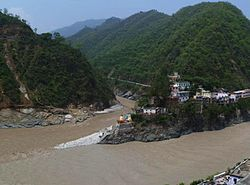 Confluence of Alaknanda (bottom, from right) and Mandakini River (flowing from top - North) at Rudraprayag.  Before 17 June 2013, there was a footbridge (jhula) over the Mandakini; this was washed away in the 2013 Uttarakhand floods.  The stones at the bottom of the stairs were not there; instead, there was a viewing platform, and a large rock called Narad Shila.