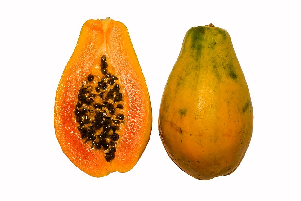 Photograph showing a papaya in cross section, with orange flesh and numerous black seeds