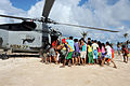 Philippine citizens approach a U.S. Navy MH-60R Seahawk helicopter assigned to Helicopter Maritime Strike Squadron (HSM) 77 as it delivers relief supplies Nov. 17, 2013, during Operation Damayan in Guiuan 131117-N-XN177-185.jpg