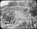 Photograph of two men starting up a vertical mine shaft underneath a small outcropping of rock on the side of a hill. - NARA - 296581.tif